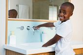 Side view portrait of smiling boy washing hands in sink at domestic bathroom poster