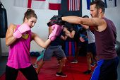 Female boxer and instructor practicing with boxing in fitness studio poster