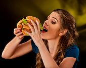 Woman eating hamburger. Student consume fast food on table. Cook teaches to cook and shares recipes. poster