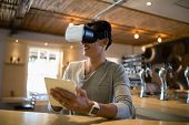 Smiling man using virtual reality headset and digital tablet in restaurant poster