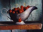 cherries in a silver gravy boat on a wooden shelf