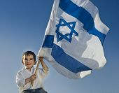 picture of israeli flag  - young boy holding the Israeli flag - JPG