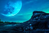 Landscape Of The Rock Against Blue Sky And Big Moon Above Wilderness Area In Forest. poster