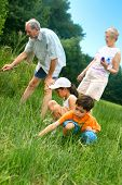 Young Children With Grandparents Looking For Insects
