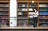 Young attractive woman standing in front of bookshelf in old university library reading a book.