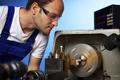 Close-up of young male technician in blue overall working on lathe machine in workshop, isolated on blue background.