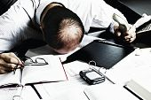 Totally desperate businessman with head on office desk top being overloaded with loads of work