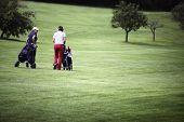 Two female golf player walking on fairway with their golf trolleys, plenty of copy-space.