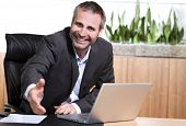 Smiling businessman behind  office desk stretching out hand for handshake, closing a business deal or agreement.