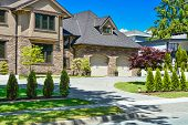 Fragment Of Luxury House With Double Garage And Concrete Driveway In Front. Front Yard Of Luxury Fam poster