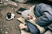 Poor Homeless Man Lying On Ground Outdoors poster