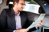 Elegant young man reading newspaper in luxury car.?
