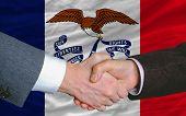 Delante de la bandera del Estado americano de Iowa dos empresarios apretón de manos después de mucho