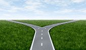 picture of paved road  - Fork in the road horizon with grass and blue sky showing a fork in the road representing the concept of a strategic dilemma choosing the right direction to go when facing two equal or similar options - JPG
