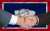 In Front Of American State Flag Of Wyoming Two Businessmen Handshake After Good Deal