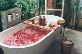 Bathtub with flower petals and beauty products on wooden tray. Organic spa relaxation in luxury Bali poster