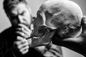 Man Smoking Cigarette Near Human Skull Symbol Of Death. Harmful Habits. Smoking Cause Health Damage  poster