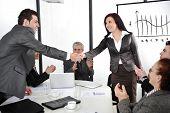 Socios estrechar las manos después de hacer reparto mientras sus compañeros aplauden