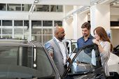 Beautiful couple smiling while examining a new car in a motor show with salesman. Mature salesman sh poster