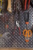 stock photo of pegboard  - Closeup of metal pegboard with tools hanging - JPG