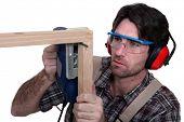 Carpenter sawing into wooden frame