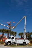 stock photo of lineman  - Electrical lineman work on high voltage power lines from the safety of a bucket on a cherry picker truck - JPG
