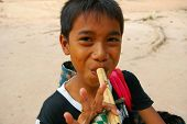 image of peddlers  - Cambodian boy playing one of the flutes he is trying to sell Bayon temple Siem Reap Cambodia - JPG