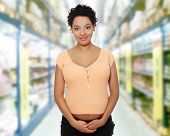 Front view portrait of a beautiful young pregnant woman in store