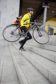 Courier delivery man in protective gear with bicycle and backpack walking up steps