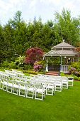 image of gazebo  - A gazebo and white chairs at a wedding venue for the ceremony and reception - JPG
