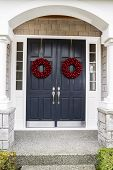 picture of red siding  - Front entrance of home door decorated with red ball wreaths for the holiday - JPG