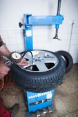 foto of air pressure gauge  - Auto mechanic in a garage checking the air pressure in a tyre with a pressure gauge   - JPG