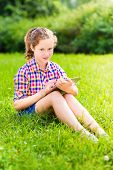 Beautiful Teenager Girl In Casual Clothes Sitting On The Grass In Sunlight With Digital Tablet