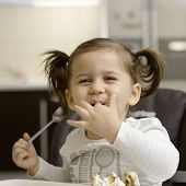 pic of inquisition  - cute little girl eating cake - JPG