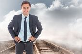 Cheerful businessman standing with hands on hips against train tracks leading over the cloudy horizon