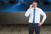 Thinking businessman tilting glasses against balcony and night sky