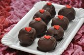 stock photo of red velvet cake  - Red Velvet Cake Pops with roses in the background - JPG