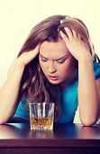 Young corpulent woman in depression, drinking alcohol