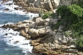 stock photo of gash  - Rocks overlooking the ocean in a great gash in Acapulco - JPG