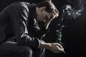 stock photo of hangover  - Depressed man smoking and drinking away his problems - JPG
