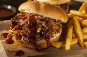 stock photo of roasted pork  - Barbeque Pulled Pork Sandwich with BBQ Sauce and Fries - JPG