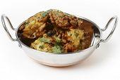 A kadai indian bowl with a pile of homemade onion bhajis