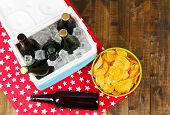 Ice chest full of drinks in bottles on color napkin, on wooden background