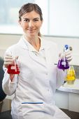Portrait of confident female scientist examining flasks with different chemicals in medical lab