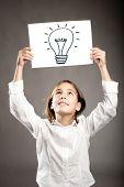 little girl holding a light bulb drawing