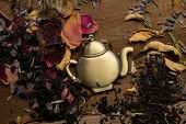 Teapot trinket among flower tea petals on wooden table background