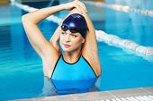 Young woman wearing blue swimming suit and cap in swimming pool