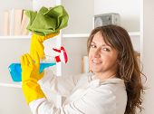 Beautiful young woman cleaning her house wearing yellow gloves with spray cleaners and cloth