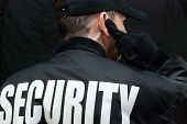 picture of bodyguard  - Close-up of a security guard listening to his earpiece. Back of jacket showing.