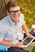education, technology and internet concept - smiling male student in eyeglasses with tablet pc outsi